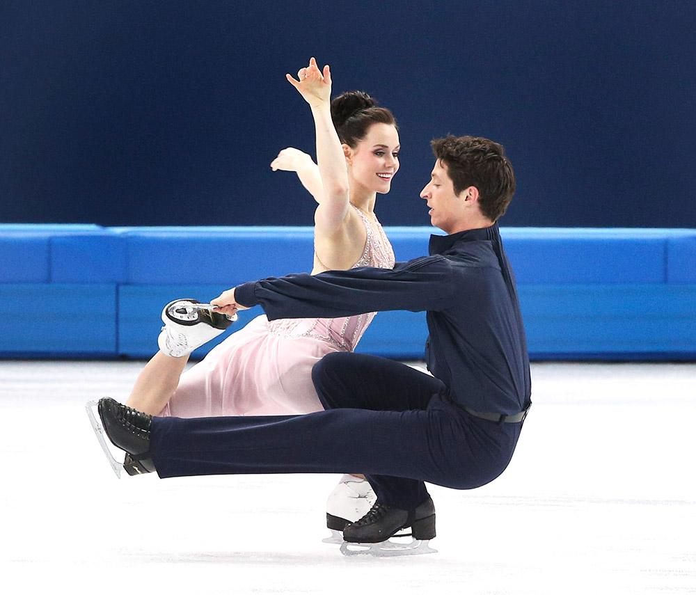 Olympic flag bearers Tessa Virtue Scott Moir-performing on ice, her in a pink dress him in all black