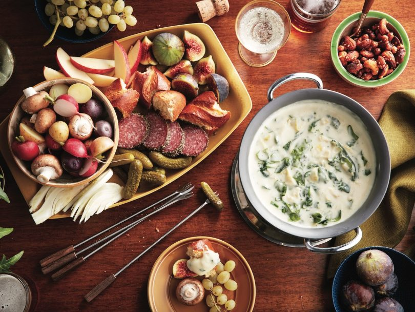 new years eve appetizers on table - spinach fondue dip, charcuterie, olives and nuts