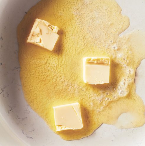 Three pads of butter melting in white pot