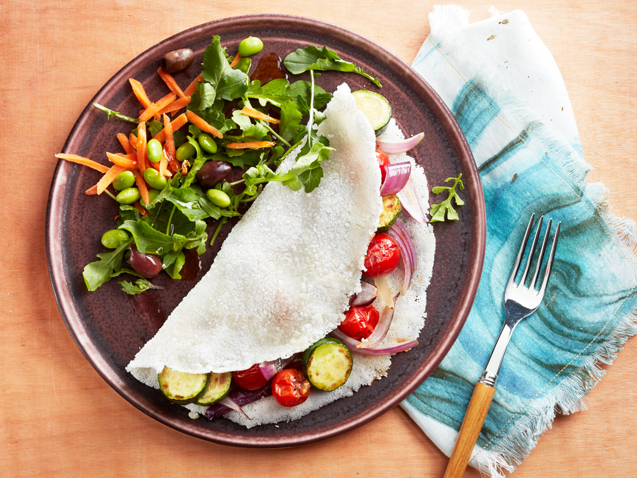 Tapioca crepe stuffed with vegetables on plate with salad