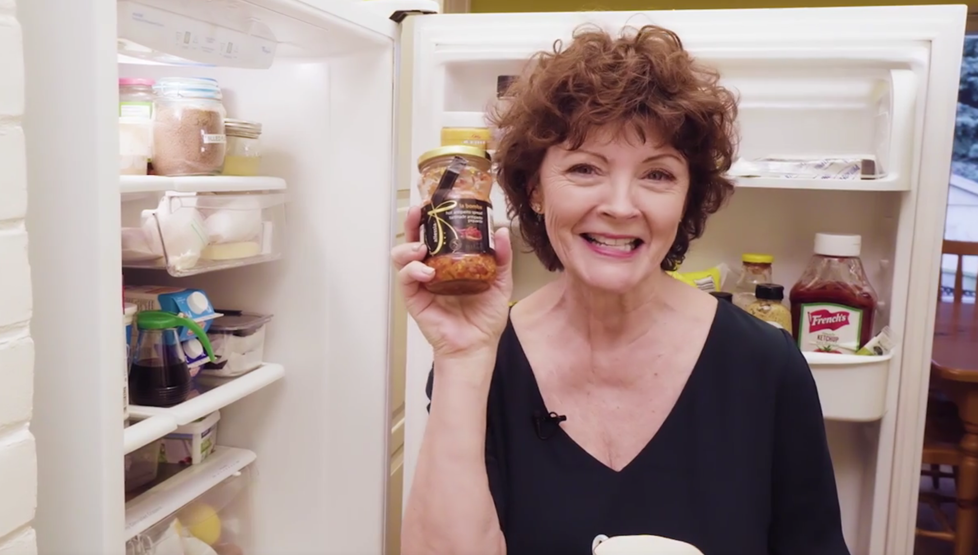 Mairlyn Smith holding a jar of sauce