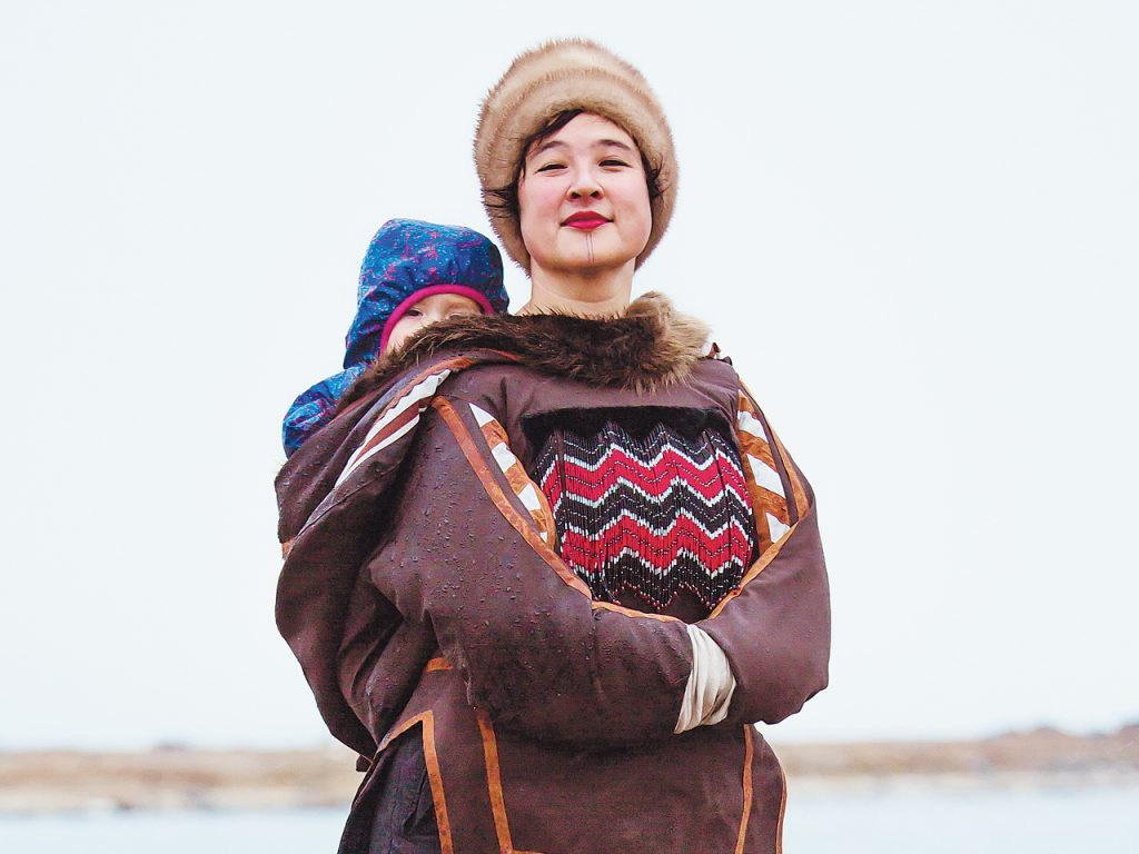 Laakkuluk Williamson Bathory poses in a traditional parka with one of her children on her back