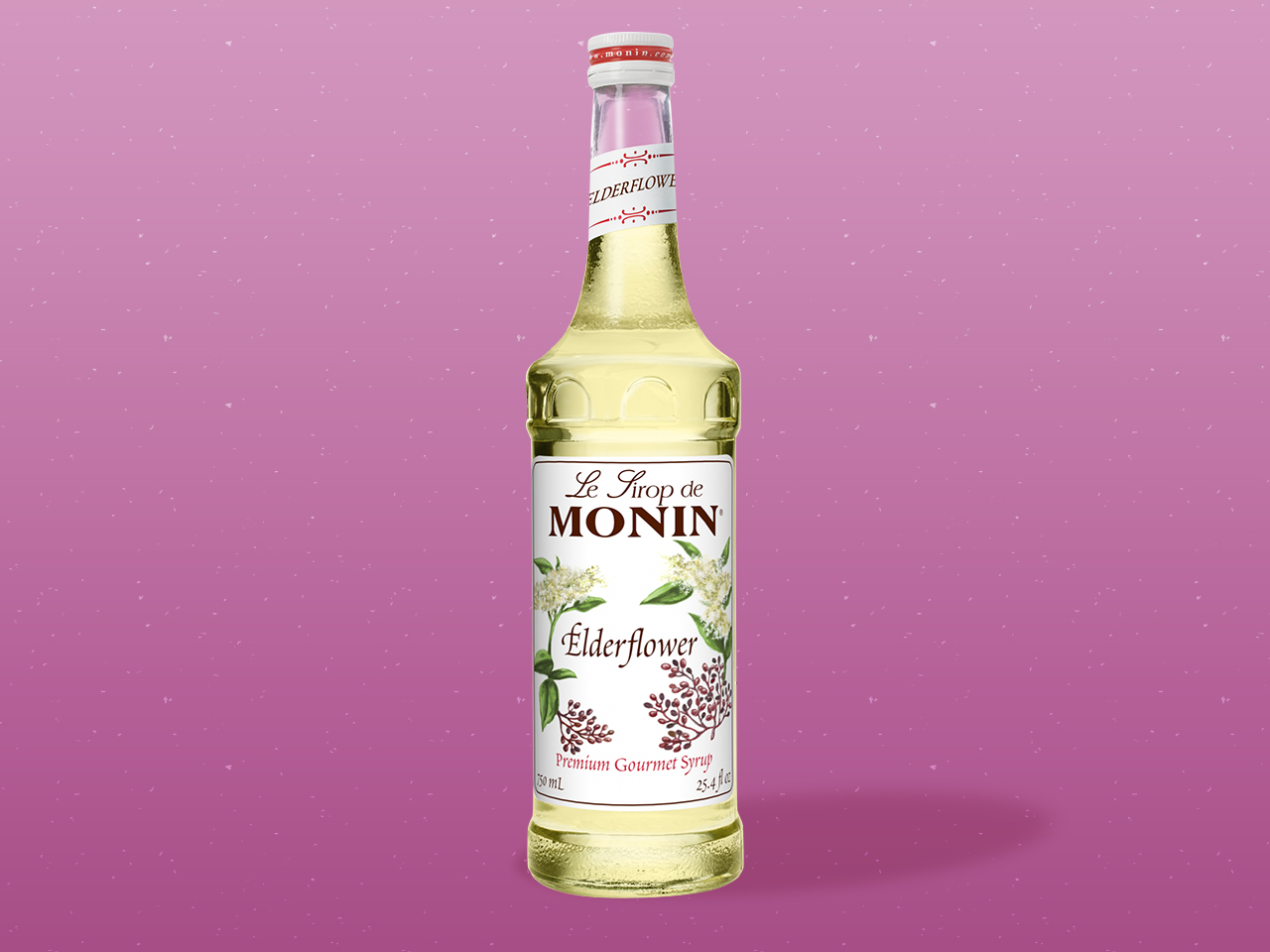 Bottle of Monin Elderflower syrup on pink background.