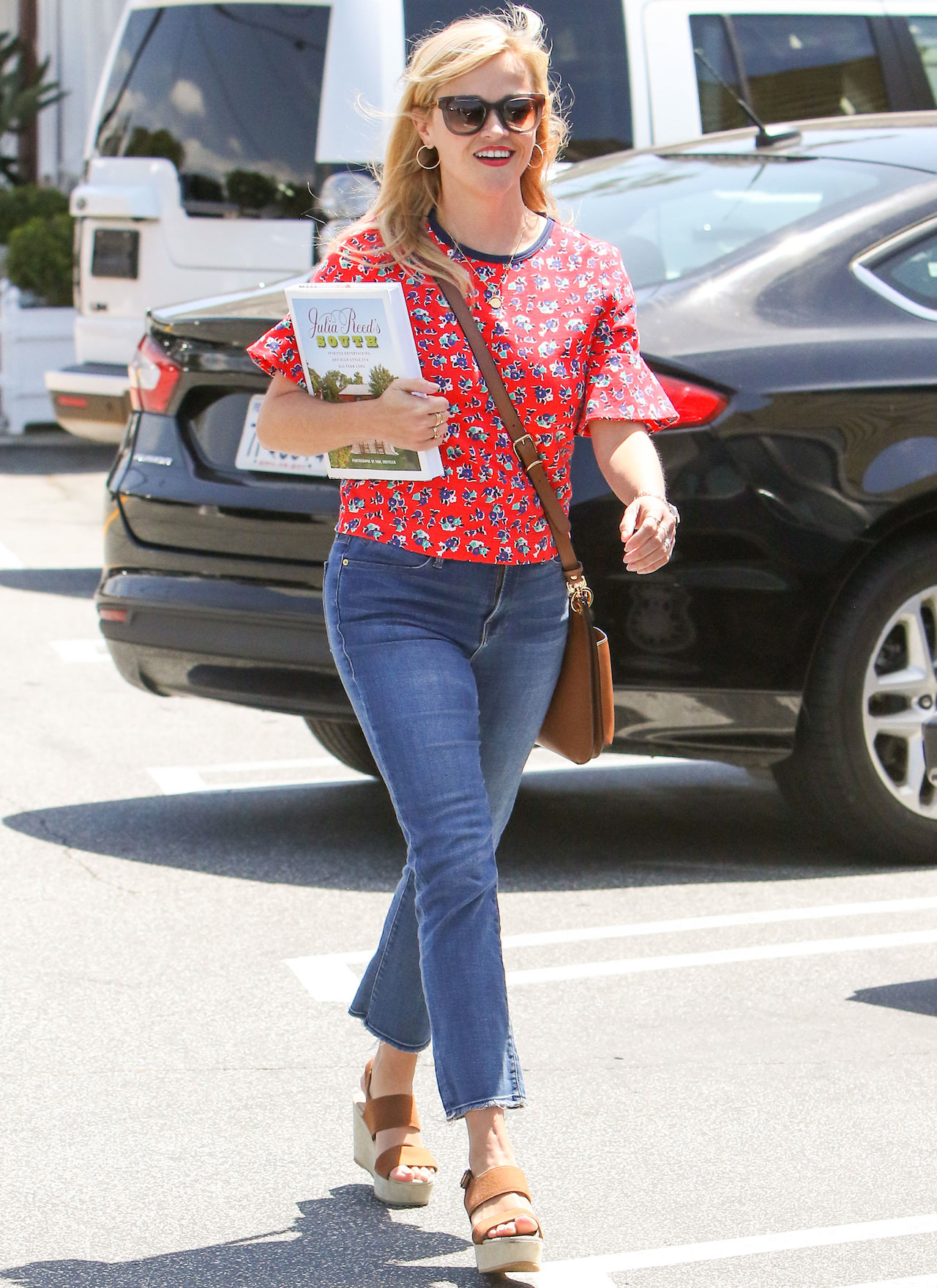 Reese Witherspoon walking down the street in jeans and a red shirt carrying a novel