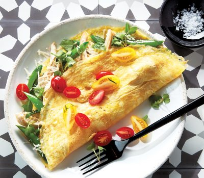 chicken omelettes filled with snap peas and basil, topped with tomatoes, served on a white plate