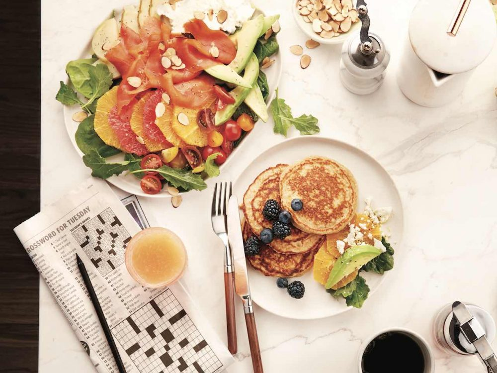 Breakfast salad with avocado and smoked salmon on a plate, served with pancakes.