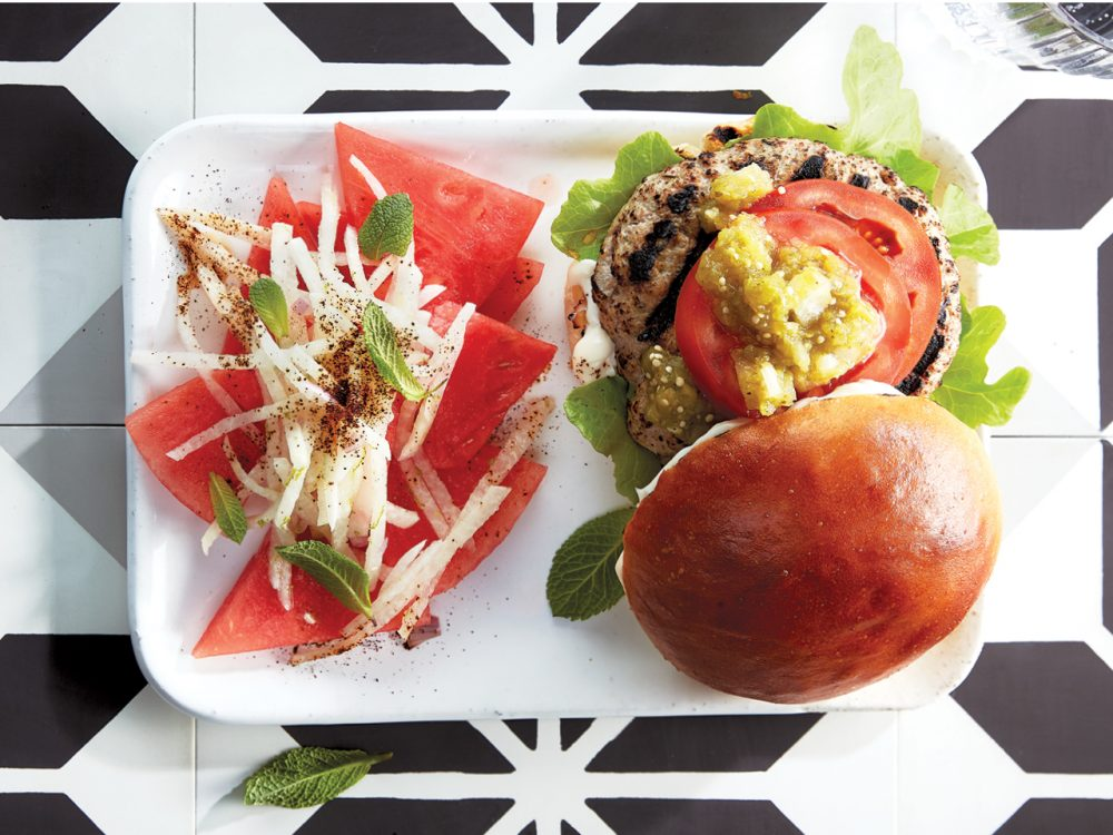 Salsa verde pork burgers with watermelon and jicama salad on a rectangular white plate