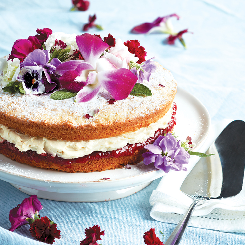 Victoria sponge cake covered in white icing and edible flowers on a white cake pedestal