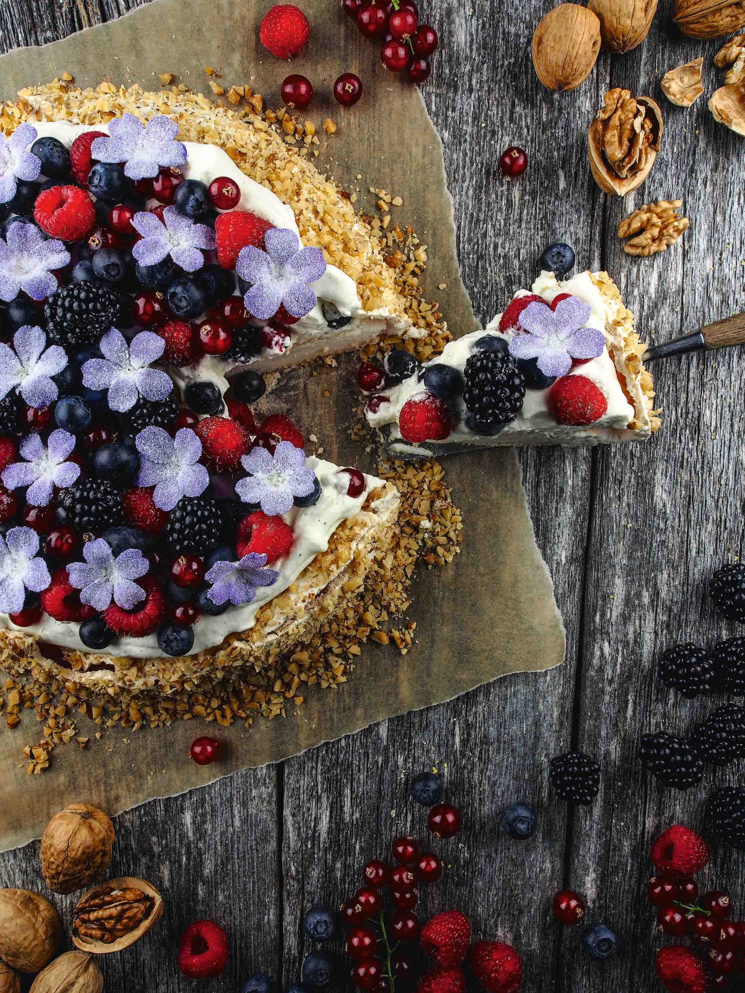Cake topped with purple flowers and berries.