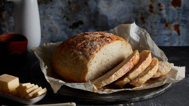 no-knead bread recipe: loaf of bread on a serving plate with three slices cut off