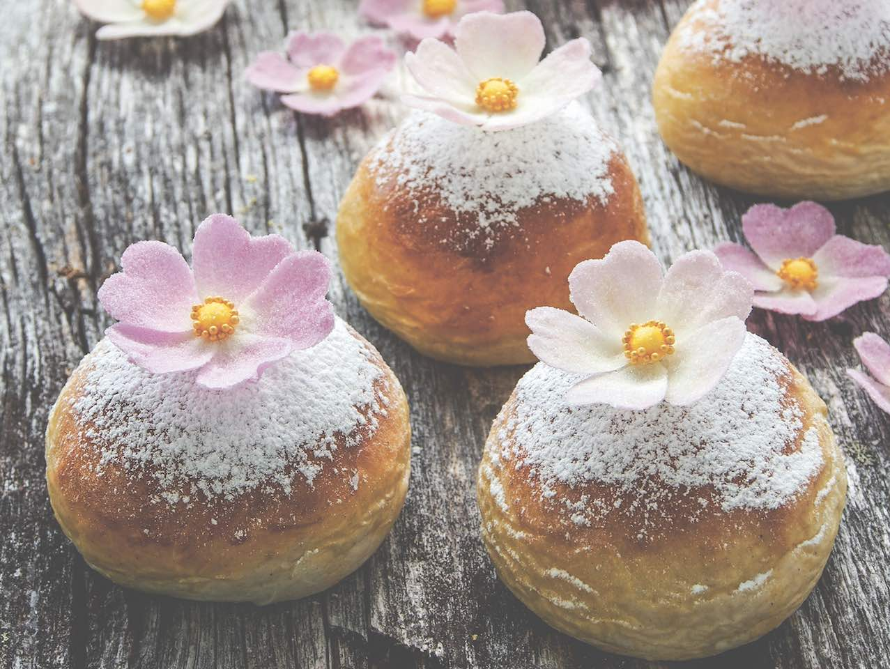Powdered doughnuts topped with pink and white flowers.