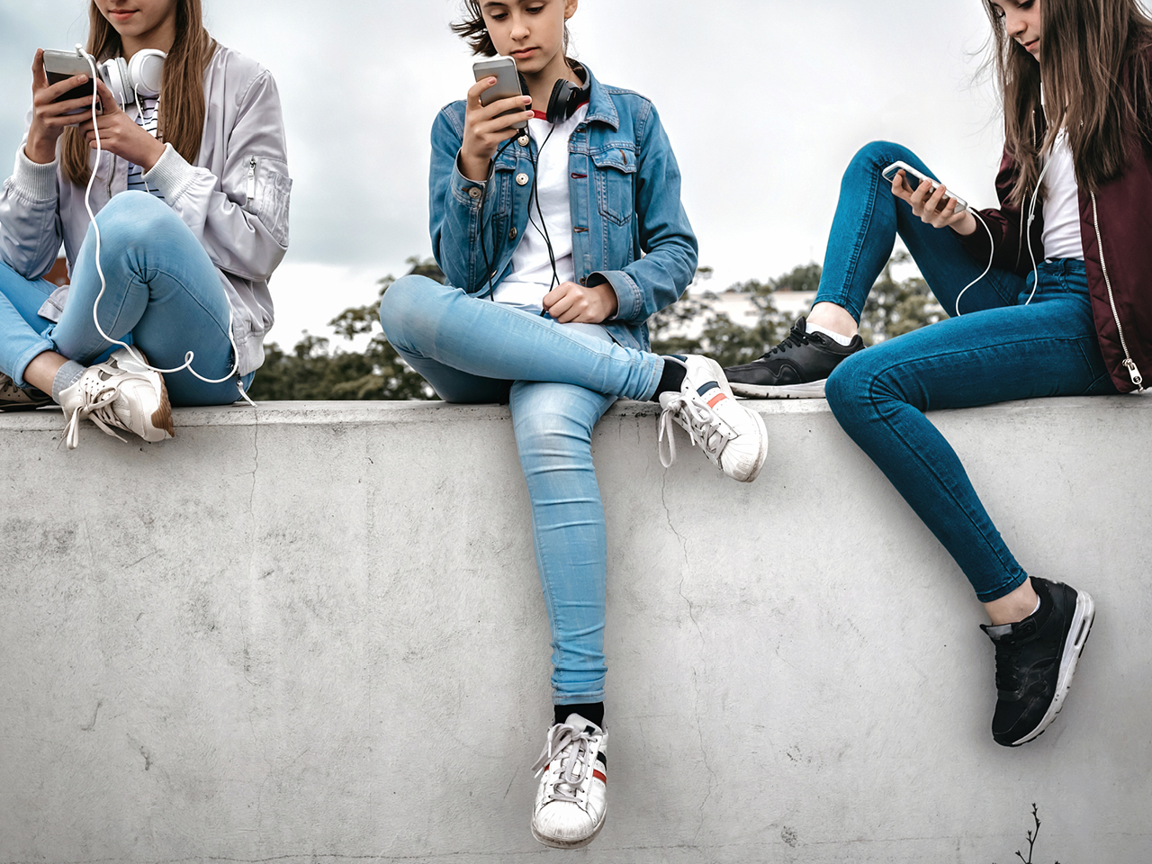 Teenage Girl On Social Media Feature Image Shows Girls Sitting On A Cement Wall While Using