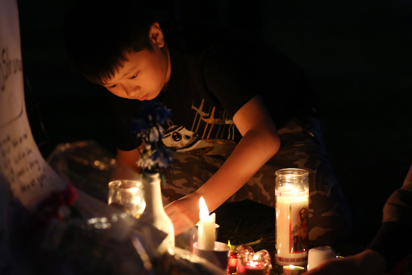 A boy lights candles at a vigil for victims of the Toronto van attack