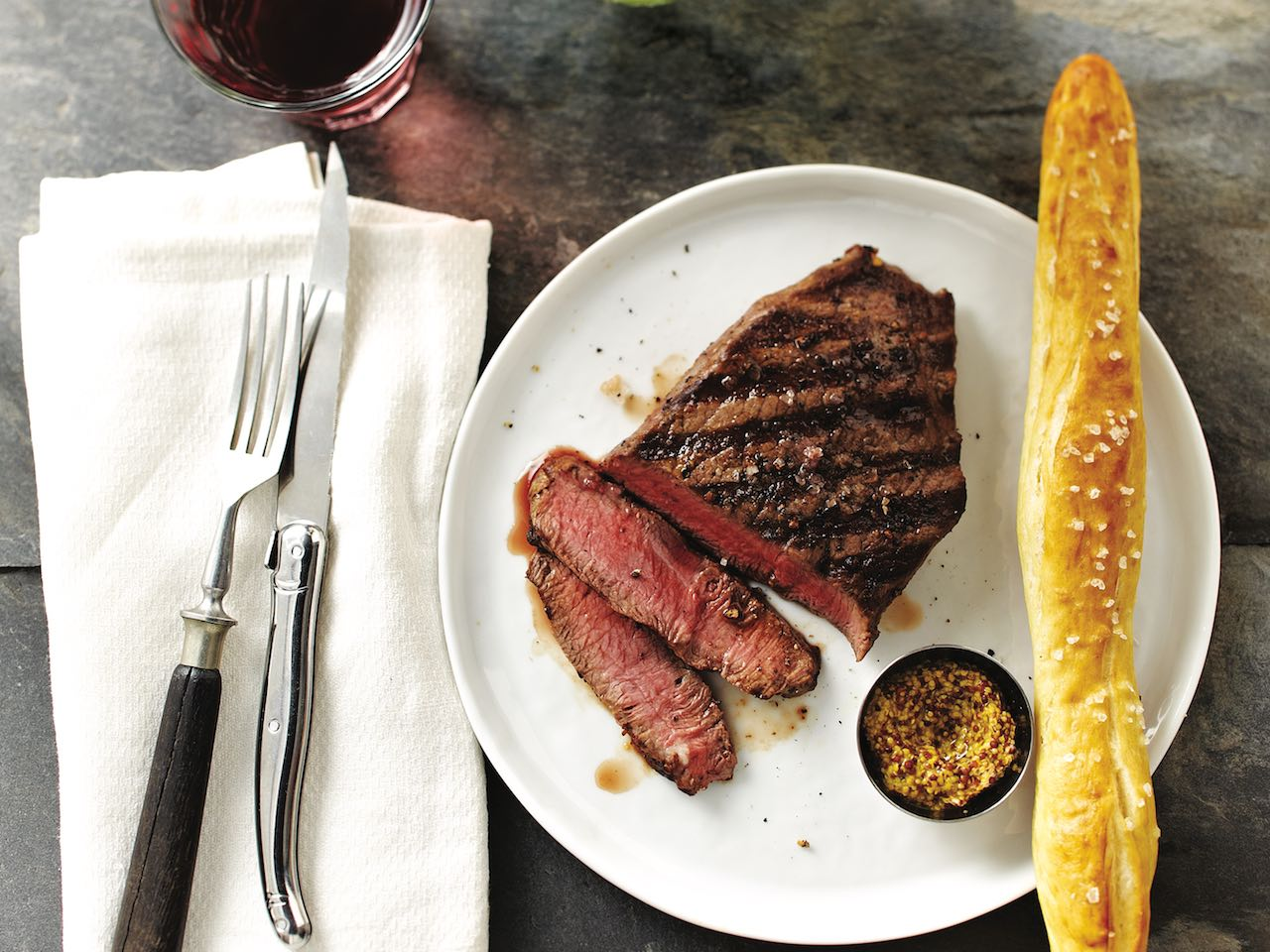 steak on a plate with a baguette