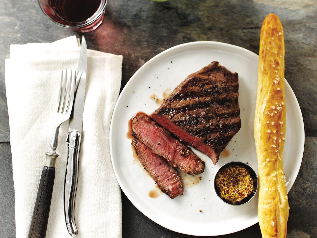 Flat iron steak cut with pretzel stick and mustard sauce