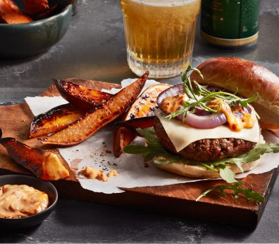 harissa burgers topped with cheese on a wooden serving tray