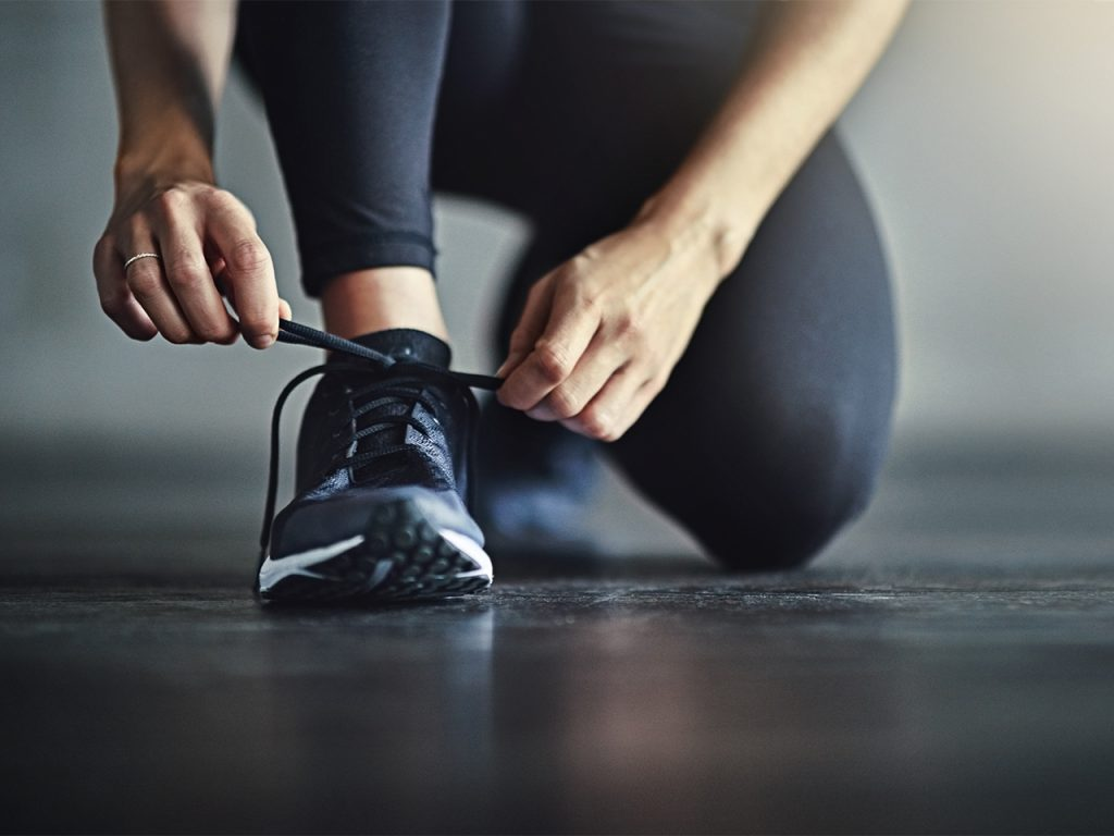 woman tying shoes in preparation for workout