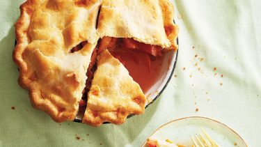 Summer pie recipe collection: Peach pie with a slice talent out on mint-green table cloth