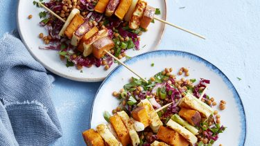 Halloumi and sweet potato skewers served on lentil salad on a blue table