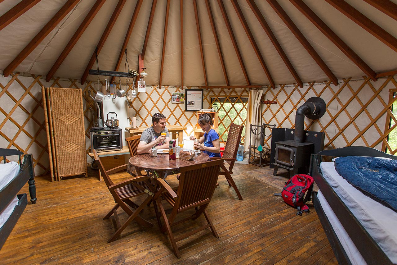 Two people sit at a table inside a yurt, a domed rounded room with wood floors and canvas covering.