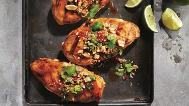 Best way to cook chicken breast: Three chicken breasts covered with peanuts and parsley on baking sheet.