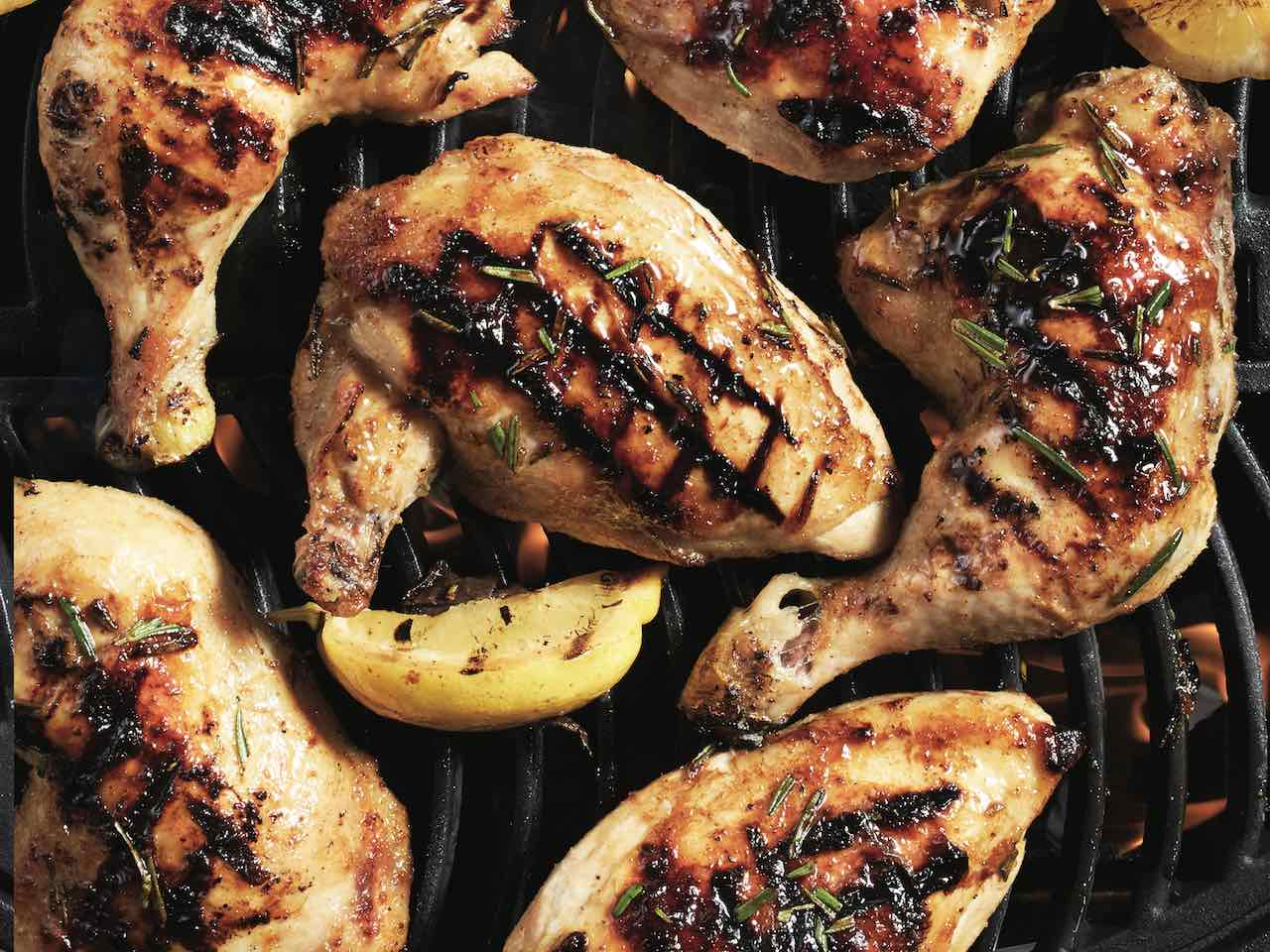 Chicken legs and lemon wedges on grill