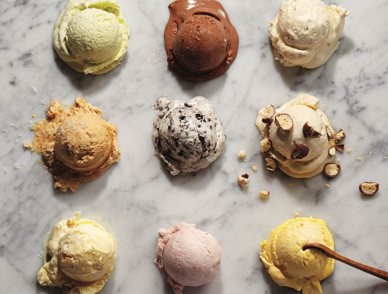 Nine ice cream scoops on marble table