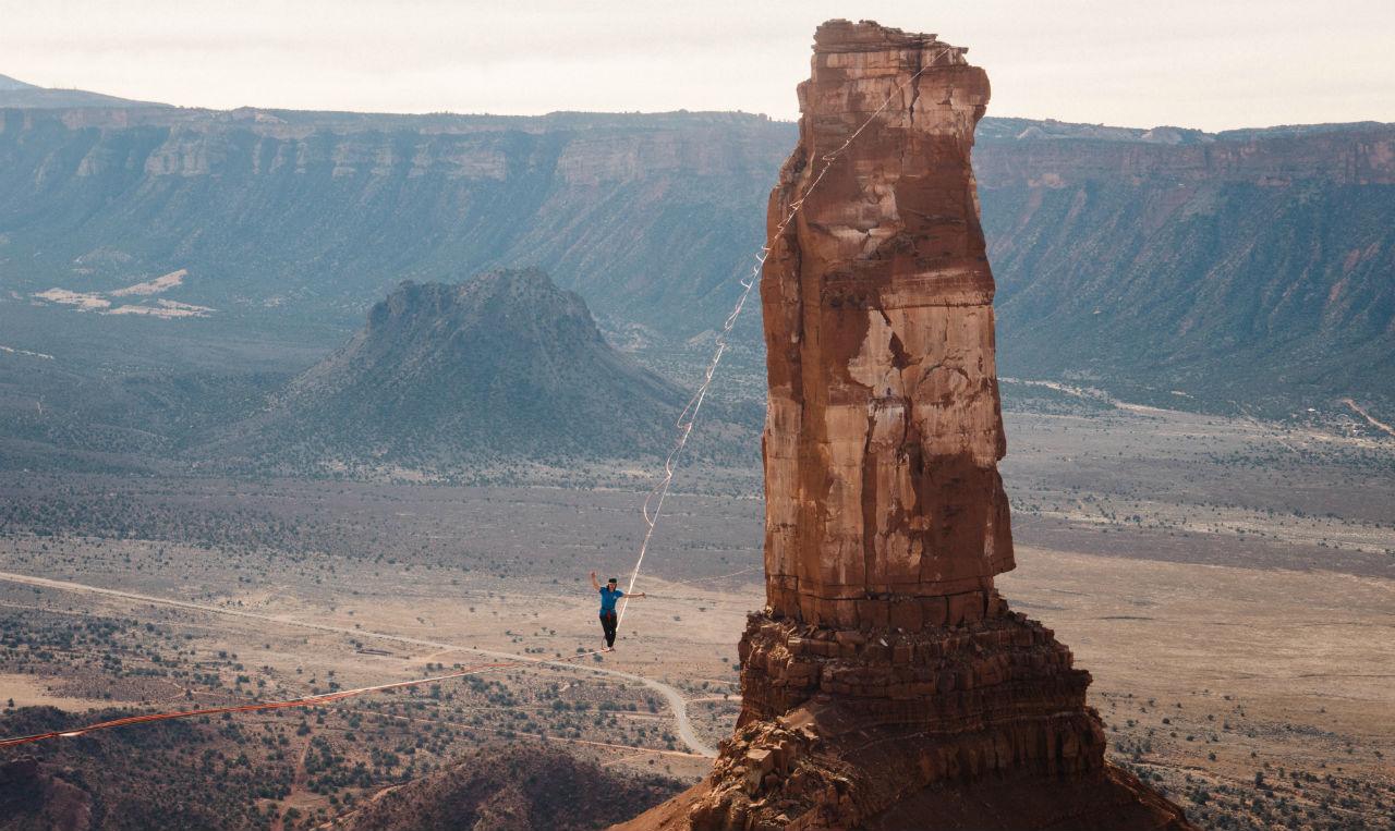 Slackliner Mia Noblet walks a slackline rigged on rock formations in Moab.