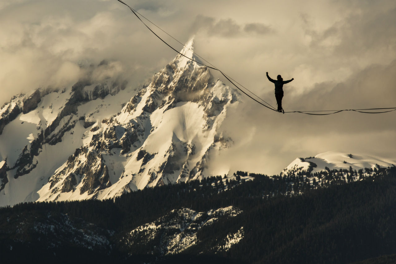 A silouhette of slackliner Mia Noblet walking a slackline high above the forest with snowy mountains in the background.