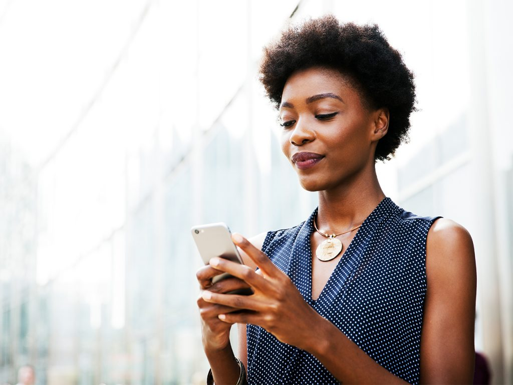 Woman looking at mobile phone. Should you trust budgeting apps like Mint?