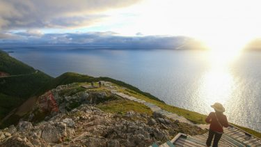 best nature spot cape breton highlands visitor in hat gazes at sunset from stairs on grassy hill