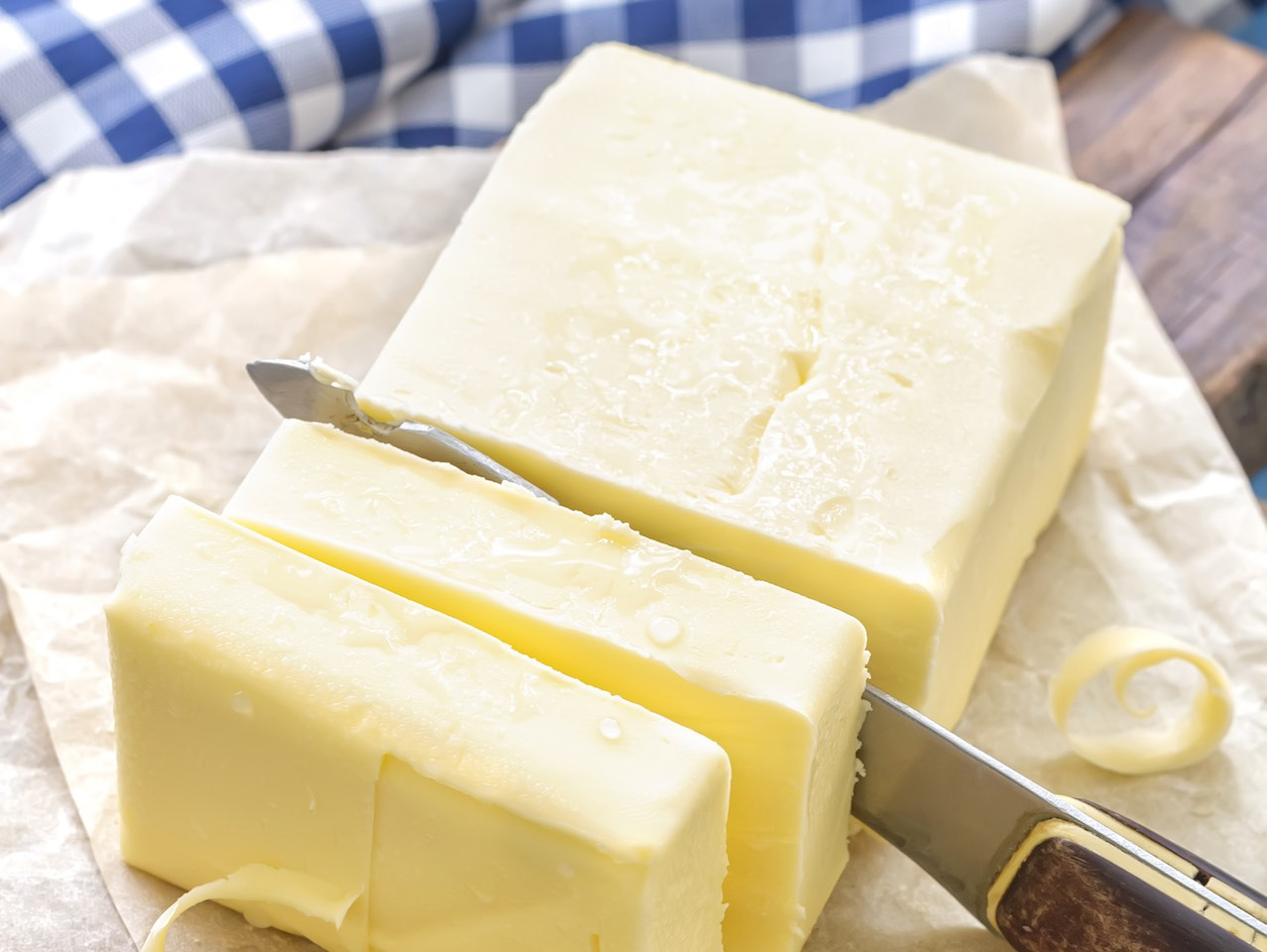 Knife slicing through slab of butter.