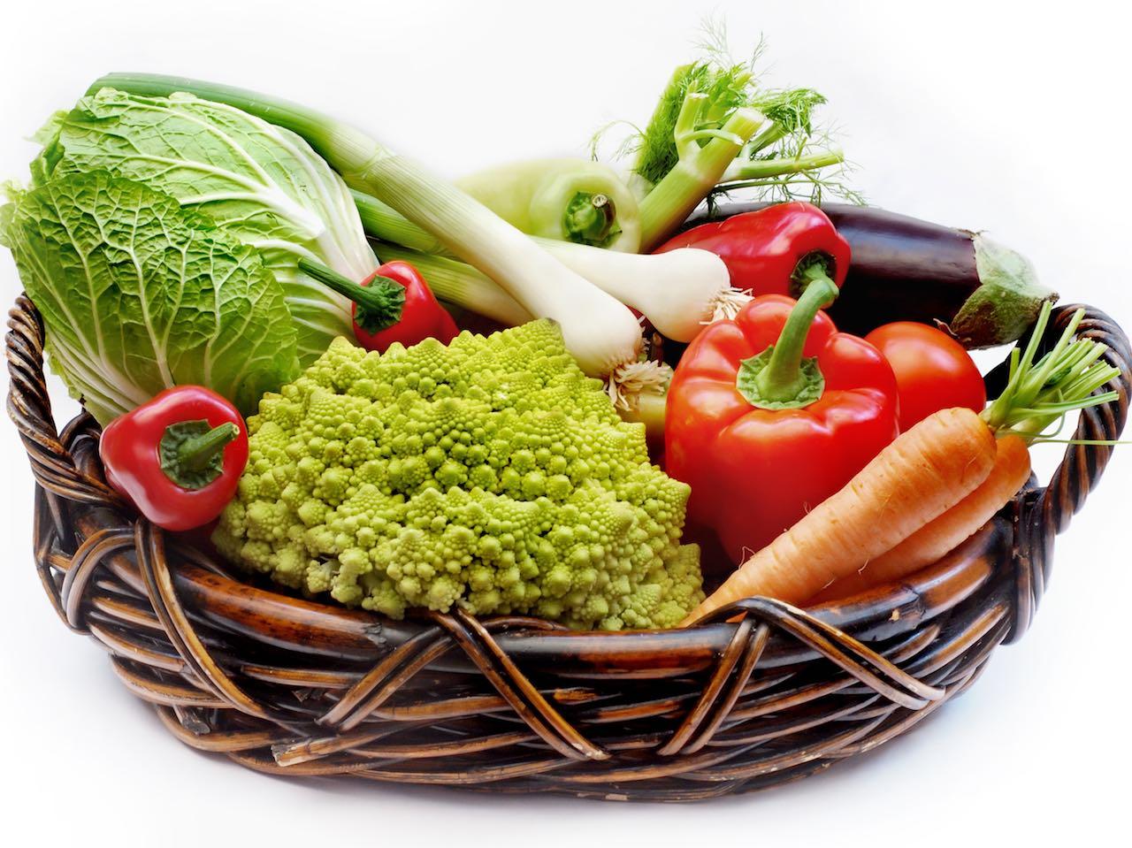 Refrigerator crisper drawer: vegetables in a wicker basket.