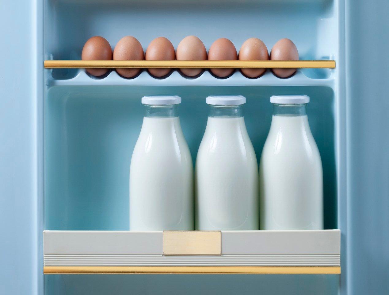 Expiry dates: 3 bottles of milk and brown eggs in retro fridge door