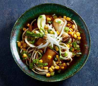Celeriac, corn, mushroom and green onions in a blue-green bowl