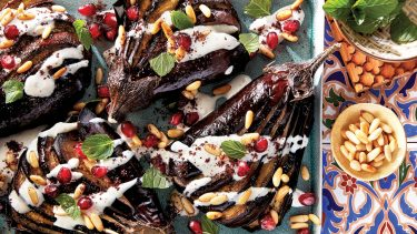 roasted eggplant recipe drizzled with tahini sauce and topped with pine nuts
