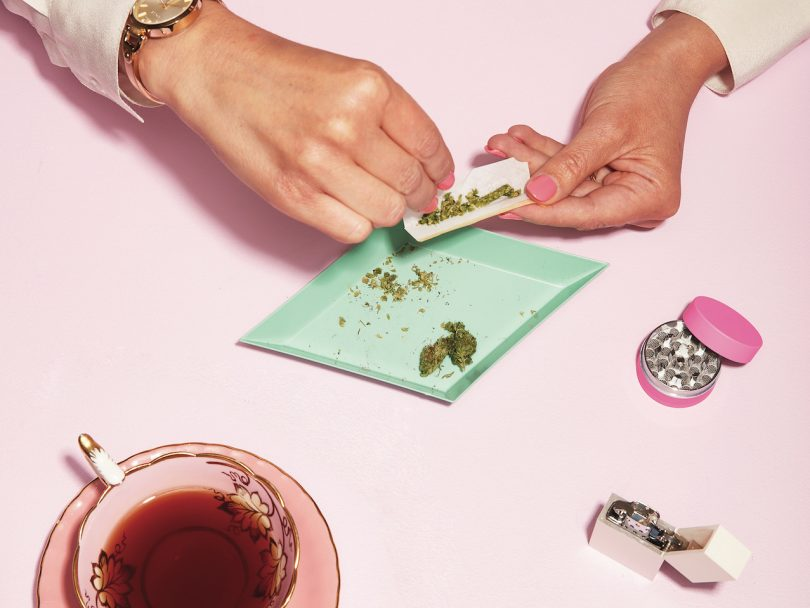 how to smoke weed - a pair of hands are rolling a joint on a pink table