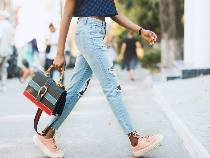 woman wearing jeans and pink sneakers carrying a handbag walking down the street