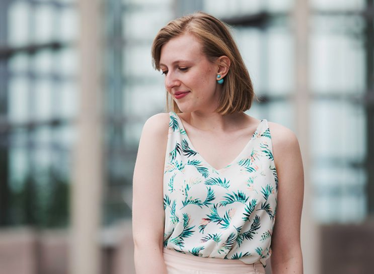 Jewish-Nose-writer-Victoria-Christie wearing a sleeveless floral shirt and beige skirt