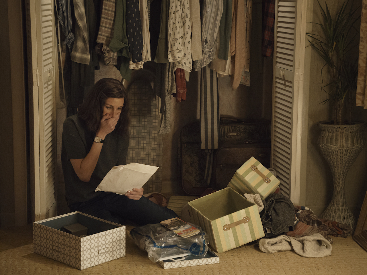 Julia Roberts Homecoming Amazon Prime-A woman kneels on the floor by her closet reading a large envelope, one hand to her mouth.