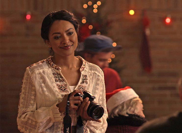 Netflix November 2018-a woman weith dark hair and a white shirt holds a camera.
