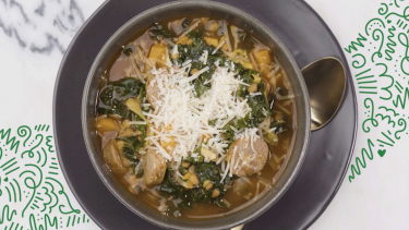 Lentil, kale and sausage soup in a bowl topped with parmesan