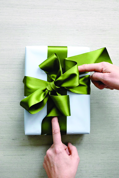 How to tie the perfect bow- two hands looping the ends of green satin ribbon back under the knot