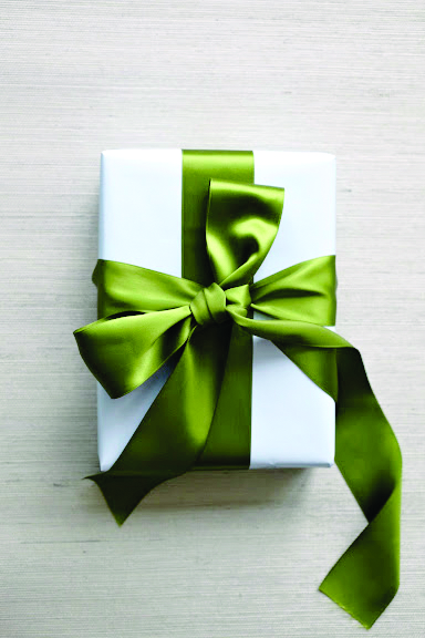 How to tie the perfect bow-one satin green bow with loose ends tied around a white box
