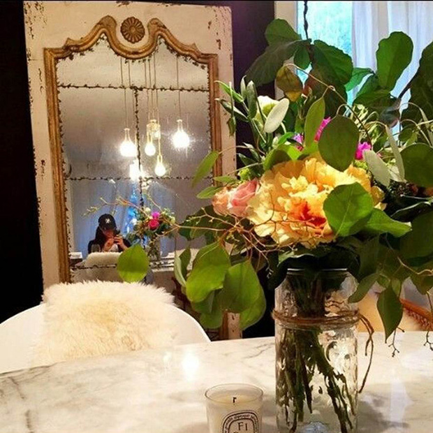 Meghan Markle Home Décor-fresh flowers in a vase sit by an elegant mirror on a marble table top