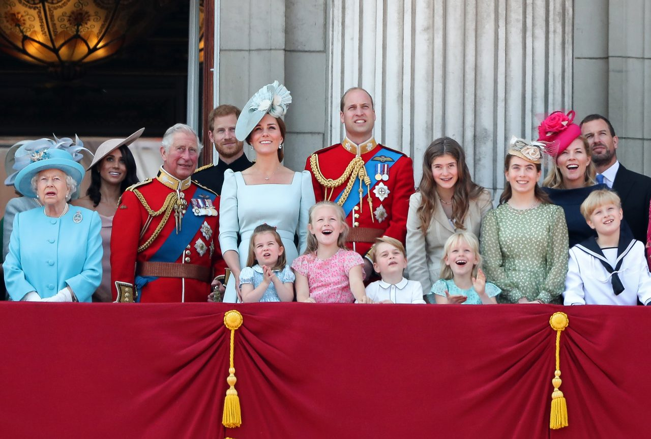 Members of the British Royal family stand on a balcony in dress attire watching the sky for Trooping the Colours 2018
