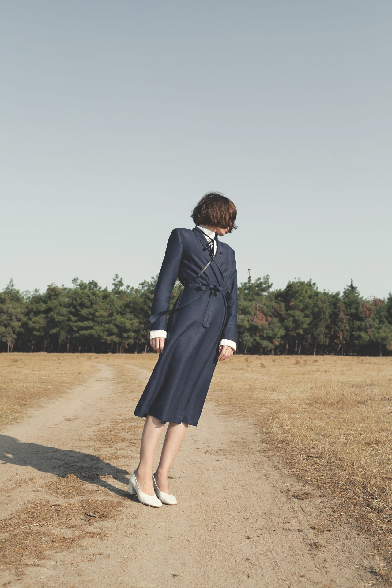 Emotional Affair-A Woman In A Blue Coat stands on a dirt road looking away from the camera