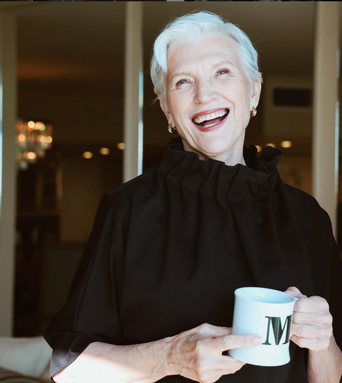 Maye Musk drinks coffee wearing a black top.