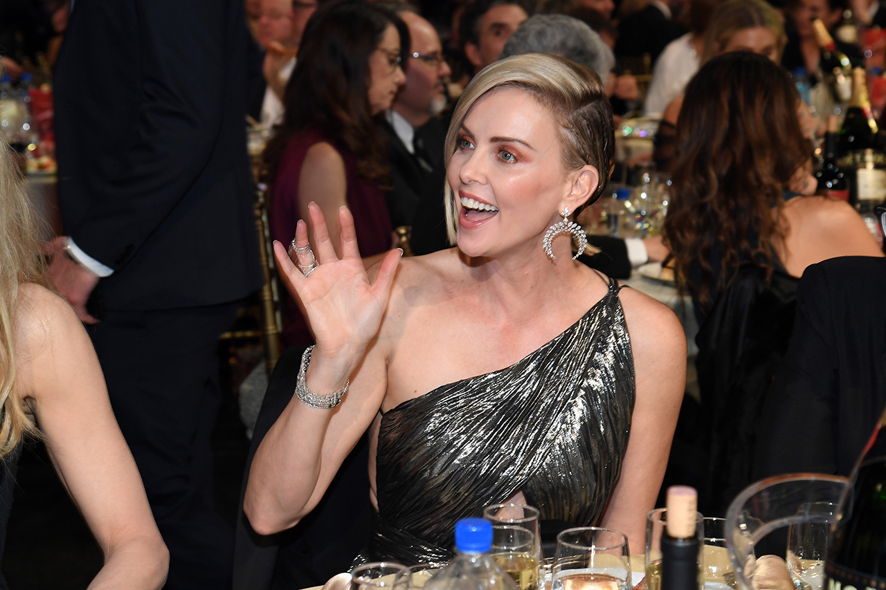Is Charlize Theron dating Brad Pitt? Theron smiles and waves from her table.