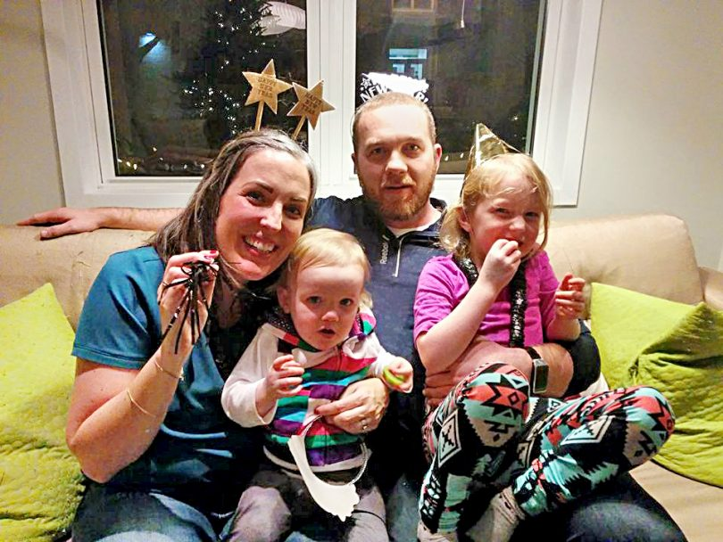 opioid addiction stigma-a family of four sit on a couch with New Years Eve decorations